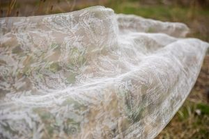 Image of a sheer white textile with ghostly forms waving in the wind outdoors