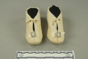 Pair of white satin children's shoes near a tape measure.