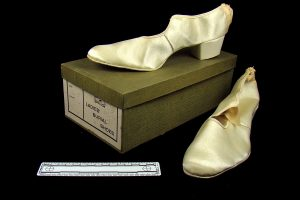 pair of ladies satin shoes with storage box on a black background