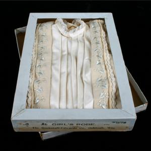 photograph of a white silk dress inside a dress box.