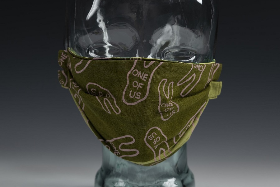 """Color photograph of a face mask mounted on a glass head form. Mask is made of a olive green cloth material with printed pink two-fingered hand designs with the words """"one of us"""" also appearing in pink text inside the hand shapes."""