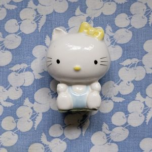 ceramic hello kitty figuring on a blue patterned textile