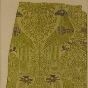 green textile fragment on a cream background showing two birds and two dragons facing each other.