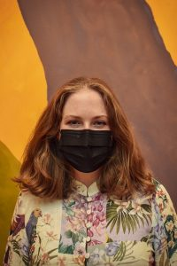 Headshot of Sophie Plzak wearing a black face mask with her hair down standing in front of an abstract painting.
