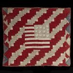 quilt on a black background sewn in red, white, and blue fabric with a backwards U.S. flag at the center.