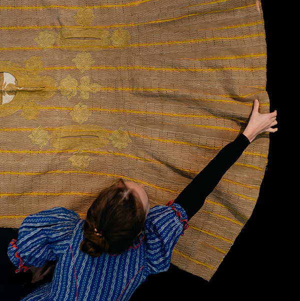 image of a woman in blue reaching across a table to move a yellow piece of fabric on a black background