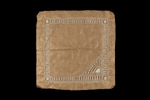 white lace sewn onto a square, light brown background