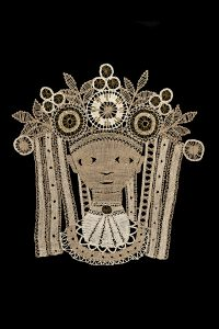 tan lace piece depicting a woman at bust length with a floral crown on a black background