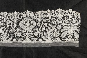 Rectangular white lace textile on a black background
