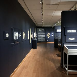 image of a gallery with dark blue walls and lace mounted on the walls