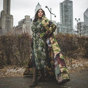 image of a woman wearing a camo coat and camo wrap and standing outside with the Chicago skyline behind her
