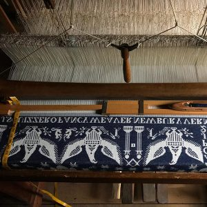 image of a wooden loom with white and blue thread being woven, creating white eagles