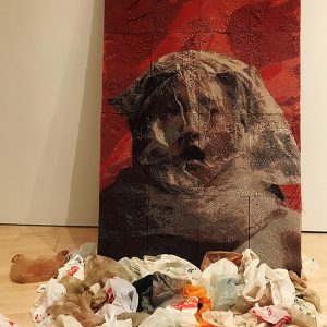 image of balled plastic on wood floor in front of a white wall with a red image of a woman with a bag over her heard behind.
